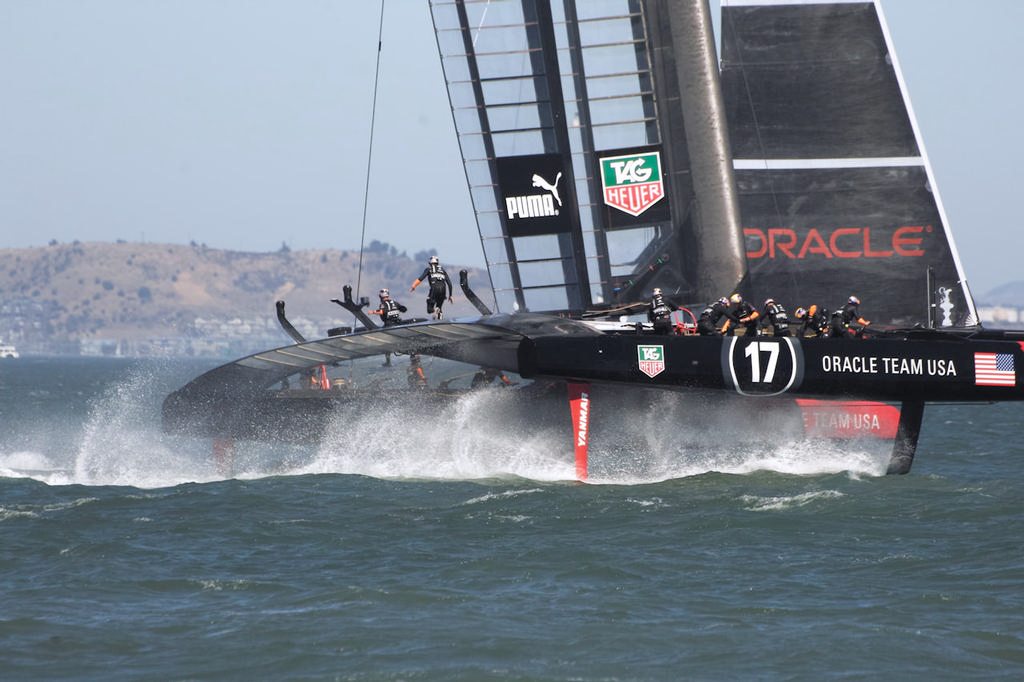 The daggerboards throw up an incredible amount of spray as Oracle continues their gybe. - America's Cup © Chuck Lantz http://www.ChuckLantz.com