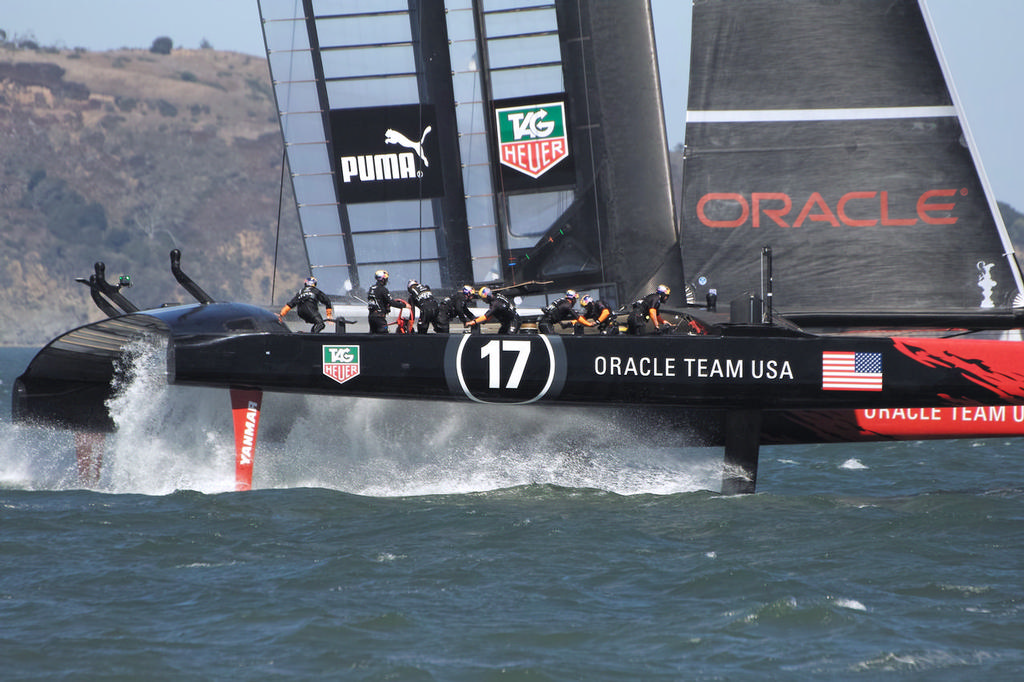 Crewman John Kostecki is the first to move across to the new side as Oracle gybes. - America's Cup © Chuck Lantz http://www.ChuckLantz.com