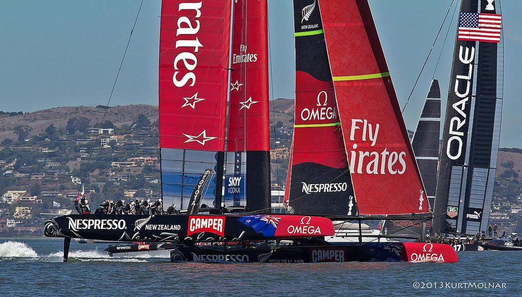 Emirates Team NZ crosses behind Oracle Team USA on Day 13, America's Cup 2013 © Kurt Molnar