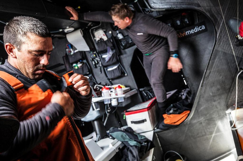 August 14, 2014. Round Britain Island Race Day 4 - OBR content Team Alvimedica: Mark Towill (L) and Dave Swete (R) gearing up to go on deck for their next 4-hour watch. Improving weather means changing to lighter gear, much of which was packed away for the rough start of the RORC's Round Britain and Ireland Race. ©  Amory Ross / Team Alvimedica
