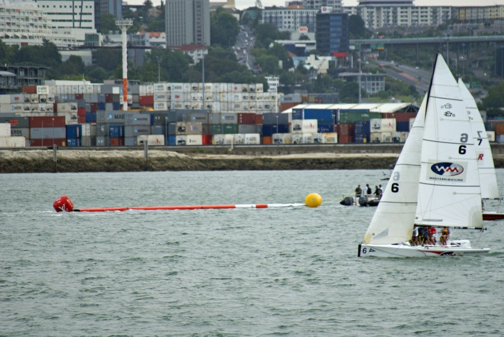 Supported by buoys TVS's wingmast is towed home by Team NZ's tender © SW
