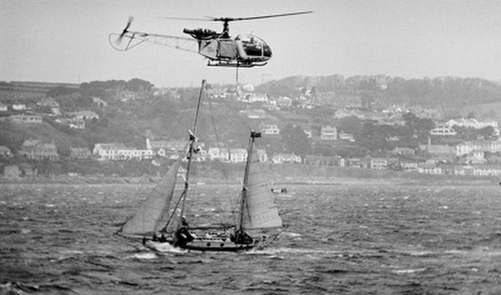 Circa 22nd April 1969: a TV helicopter hovers  overhead as Robin Knox-Johnston sails his 32ft yacht SUHAILI off Falmouth, England after becoming the first man to sail solo non-stop around the globe. Knox-Johnston was the sole finisher in the Sunday Times Golden Globe solo round the world race, having set out from Falmouth, England on 14th June 1968 © Bill Rowntree - PPL http://www.pplmedia.com