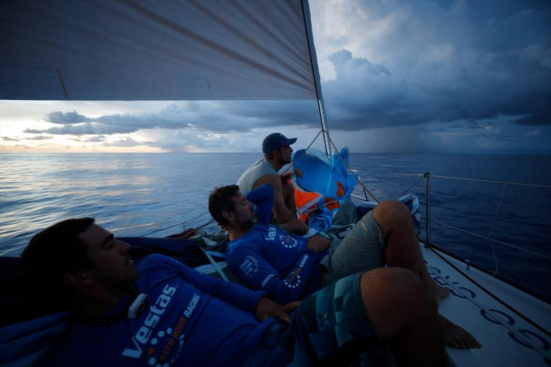 Leg 4, Melbourne to Hong Kong, day 11, rain clouds line the horizon at sundown while Nick Dana, Simon Fisher `SiFi` and Mark Towill await their influences on board Vestas 11th Hour. photo copyright Amory Ross / Volvo Ocean Race taken at  and featuring the Volvo One-Design class