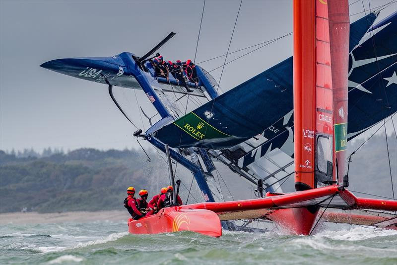 China SailGP Team sails past as the United States SailGP Team's F50 capsizes slowly after a turn during race one. Race Day. Event 4 Season 1 SailGP event in Cowes, Isle of Wight, England, United Kingdom. - photo © Ian Roman for SailGP
