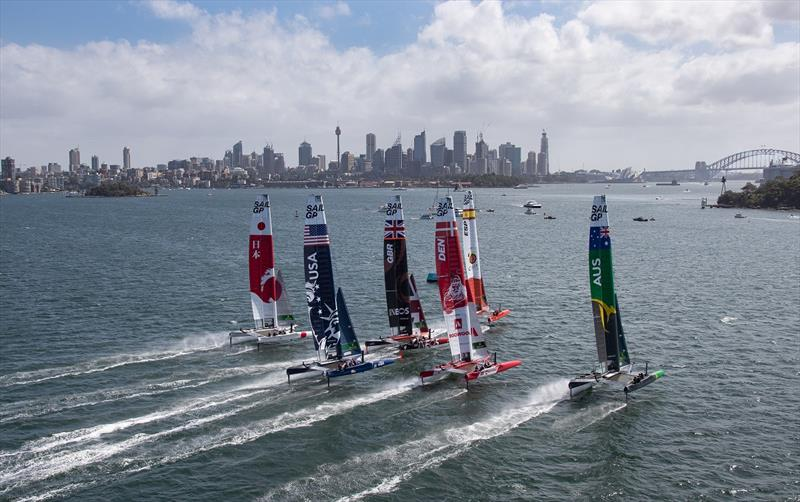 Aerial view of the fleet racing side by side with Sydney Harbour Bridge in the distance, during practice ahead of the Sydney SailGP, Event 1 Season 2 in Sydney Harbour, Sydney, Australia. © David Gray for SailGP