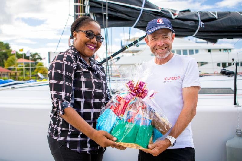 A welcome basket of Grenadian specialities is handed over to Kuka3's owner on arrival by Chinel Sandy from the Grenada Tourism Authority - 2018 RORC Transatlantic Race - photo © RORC / Arthur Daniel