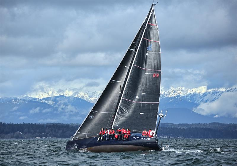 Joy Ride flashes her undercarriage as Washington State's Olympic Mountains flash their snowy slopes through the clouds - photo © Jan's Marine Photography