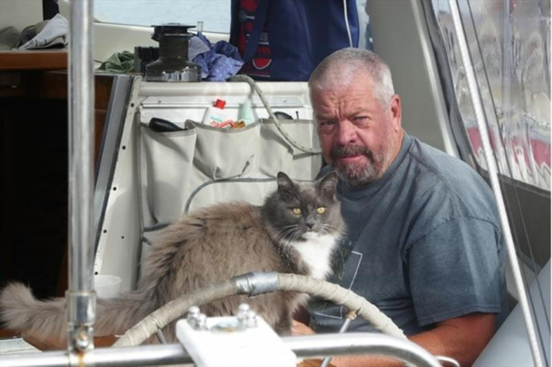 Mike enjoys a cup of coffee in the cockpit of Tamure ll, attended by his faithful cat - photo © Lisa Benckhuysen
