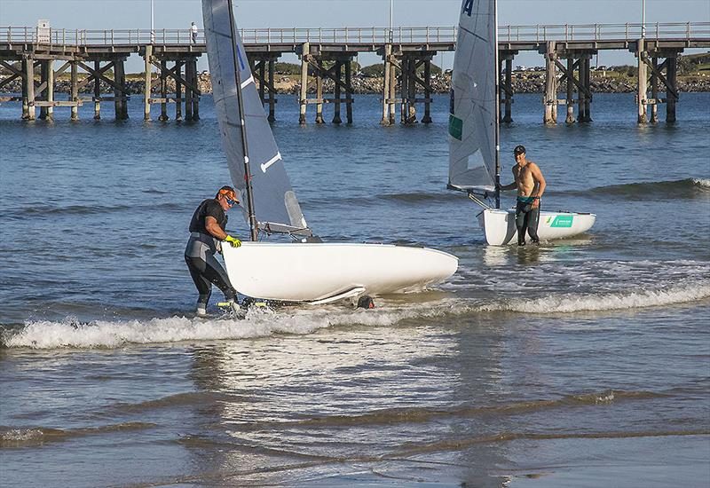 The legend that is Anthony 'Nocka' Nossiter with his Finn on the dolly as Olympian Jake Lilley also comes ashore after training. - photo © John Curnow