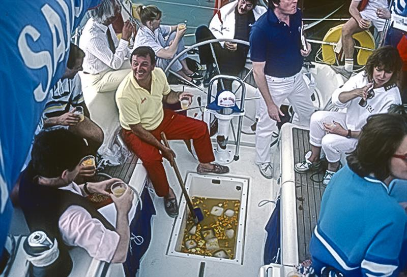 Bob Fisher hosting a party aboard Barracuda of Tarrant serving (sponsored?) rum punch from the liferaft well. - photo © Guy Gurney