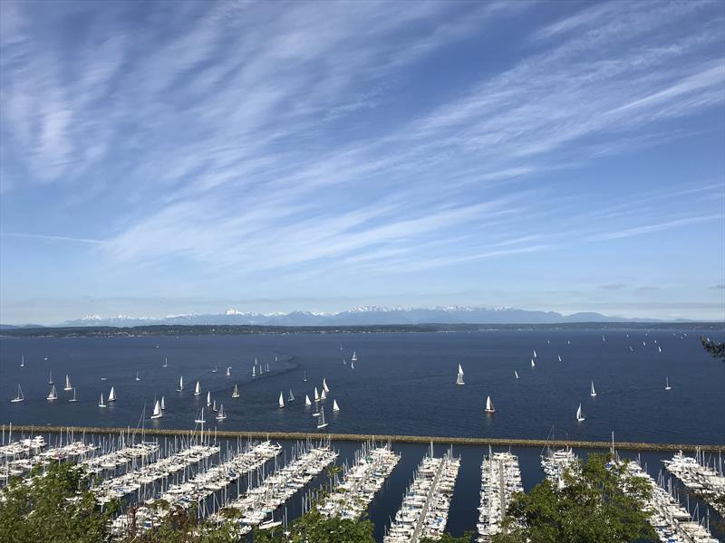 Yachts assemble off of Seattle Shilshole Bay Marina for the start of a distance race under clear skies, with the Olympic Mountains to the west - photo © Coreen Schmidt