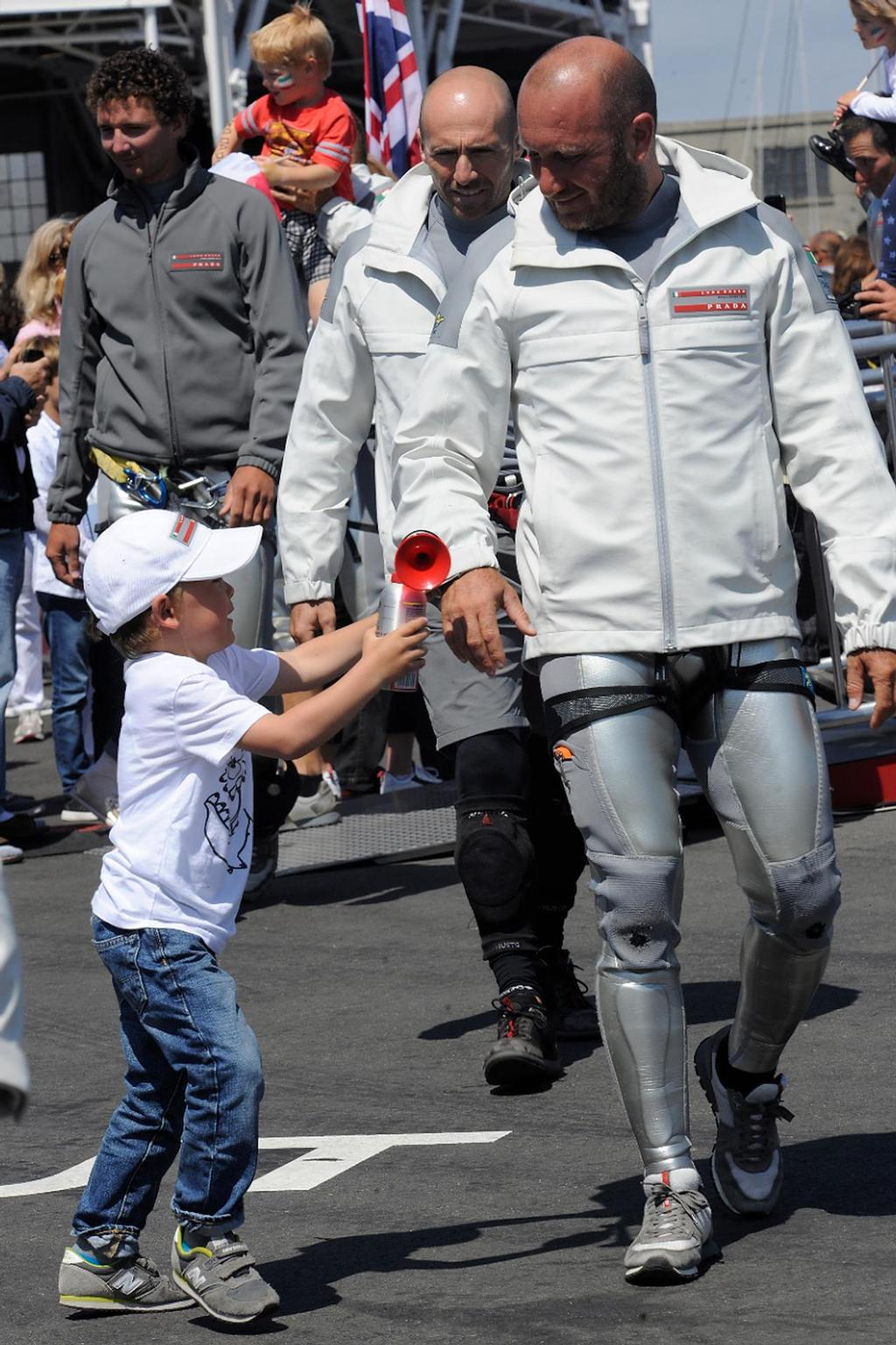 Max Sirena's son Lorenzo, 4, wants to give his Dad a horn before he goes out to sail on August 21, 2013 at the Louis Vuitton Cup in San Francisco California. ©  SW