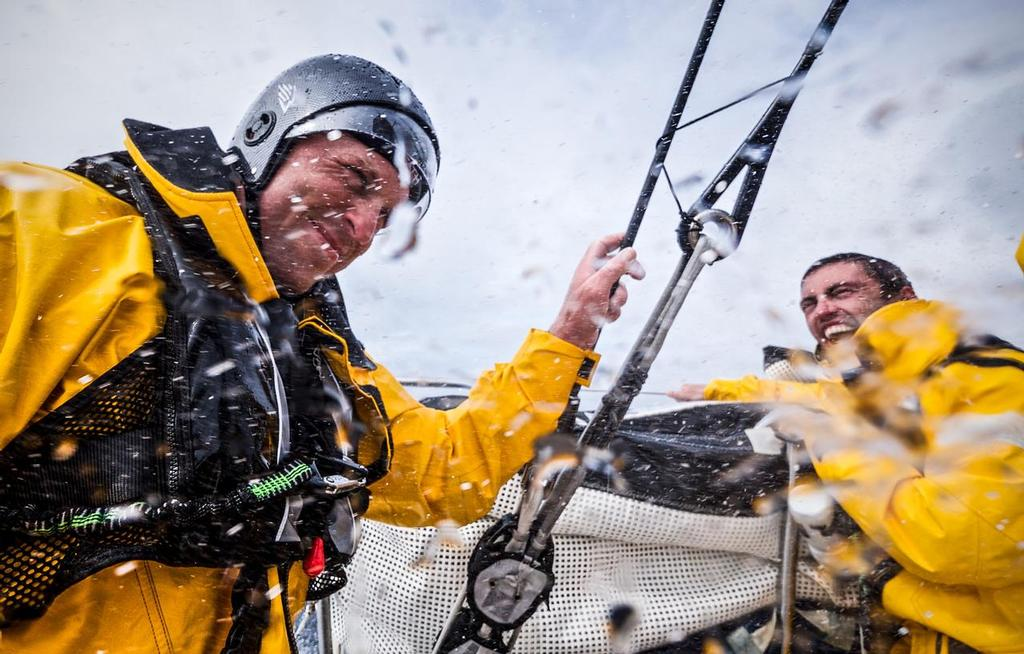 August 12, 2014. Round Britain Island Race Day 2 - OBR content Team Alvimedica: Alberto Bolzan laughs at the fact that Dave Swete can't get his helmet off after his driving stint during day two of the RORC's Round Britain and Ireland Race. ©  Amory Ross / Team Alvimedica