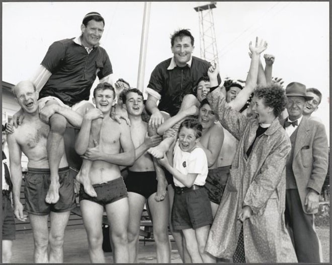 Members of the 9th St Kilda-Elwood Sea Scouts chair the Australian pair of Rolly Tasker and Malcolm Scott after their win on the first day of the 12 sq. m. Sharpie Class, Olympic Games, Port Phillip Bay, Victoria, 1956 - Australian sailing legend Rolly Tasker sails away © Bruce Howard