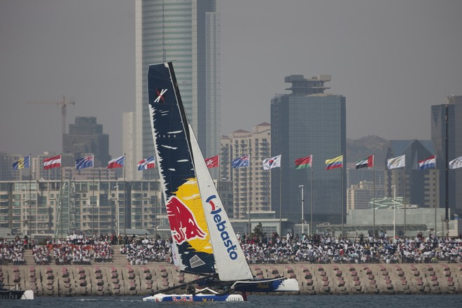 Red Bull Sailing Team flying a hull in front of spectators lining the breakwater in Fushan Bay - Act 2, Day 1, Extreme Sailing Series 2012 © Lloyd Images http://lloydimagesgallery.photoshelter.com/
