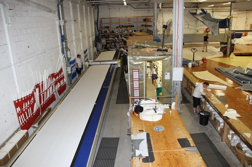 The 22metre long plotting table is not long enough for some panels in the J class spinnakers and the some have to be cut and joined. The numbered blue and red bags for panel storage/collection are on the wall behind the plotter. Note The sailcloth walled