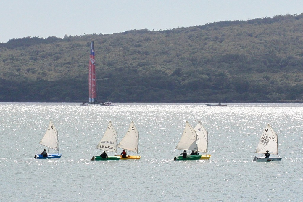 A Learn to Sail class at Wakatere BC crosses the AC72 as it sets up the other side of the Rangitoto Channel on Day 10  - Emirates Team NZ AC72 October 11,2012 © Richard Gladwell www.photosport.co.nz