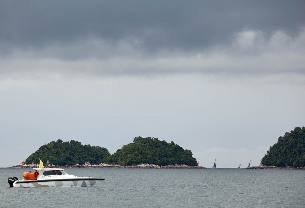 Raja Muda Selangor International Regatta 2012 - Start Boat 2 watches there fleet disappear round the corner of Pangkor Laut © Guy Nowell / RMSIR