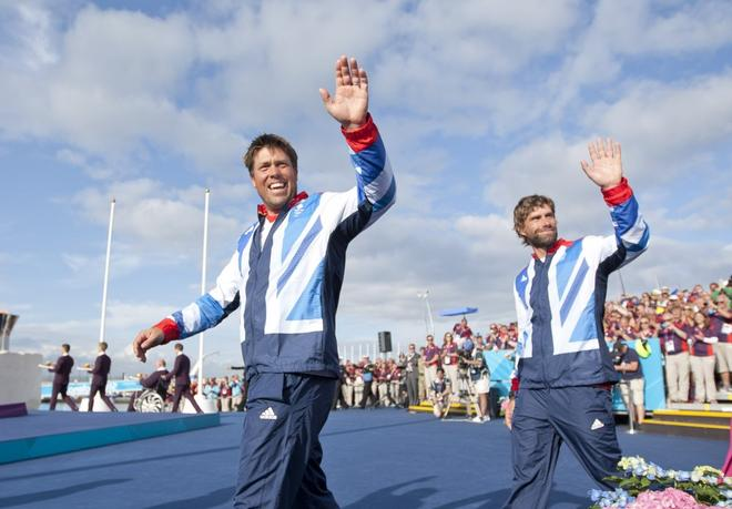 Iain Percy (right) and his mate of 25 years, Andrew Simpson (GBR), acknowledge the crowd at the medal ceremony for the Men's Keelboat (Star) event in the London 2012 Olympic Sailing Competition. © onEdition http://www.onEdition.com