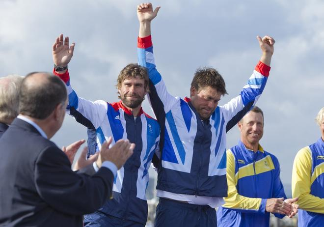 Iain Percy (left) and Andrew Simpson (GBR), acknowledge the crowd at the medal ceremony for the Men's Keelboat (Star) event in The London 2012 Olympic Sailing Competition. © onEdition http://www.onEdition.com