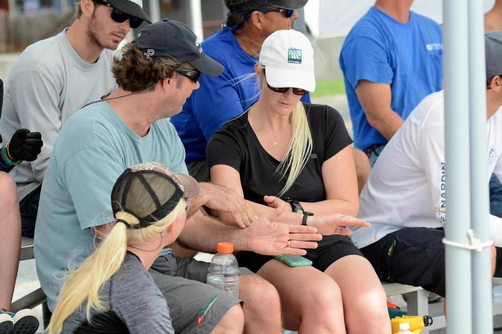 The USA's Dave Perry (left facing) talks tactics with Canada's Elizabeth Shaw while Shaw's crew, Antilles School junior sailor, Paige Clarke (lower left), from St. John, looks on.  Credit: Dean Barnes  © Dean Barnes