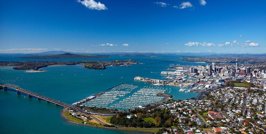 Auckland and the Waitemata Harbour. The Harbour Bridge to the North Shore is in the foreground. Behind that is the Westhaven marina with the Royal New Zealand Yacht Squadron. The pile mooring area is one option to be reclaimed for Cup bases, the other is the tank farm, on Wynyard Point immediately behind the pile mooring area and due to be leveled in 2022 and turned into Wynyard Park. Emirates Team New Zealand operates out of an oil company administration office alongside a couple of silo towers at the start of Wynyard Point. The America's Cup is expected to be raced to the left of Rangitoto Island in the far background. © SW