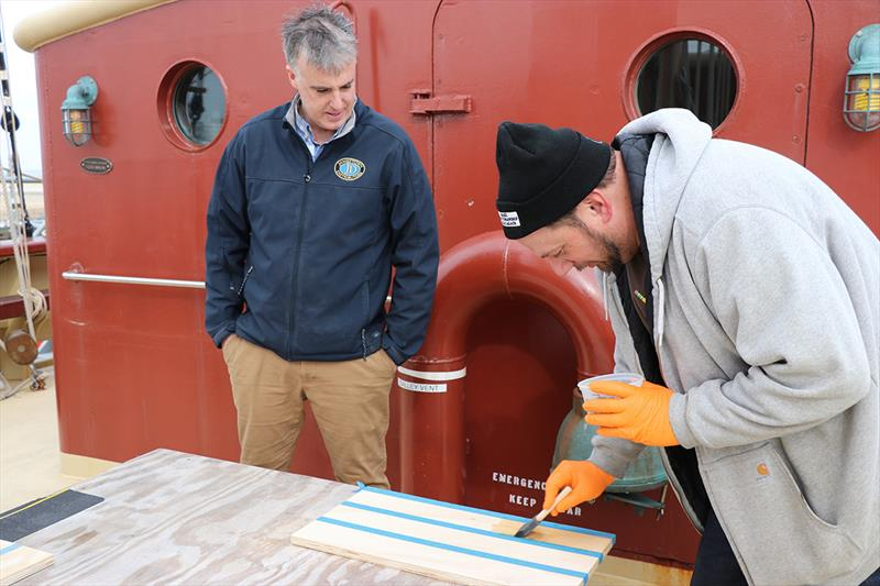 Dan O'Connor from Jamestown Distributors instructs a student in the application of varnish. - photo © Lisa Goodwin